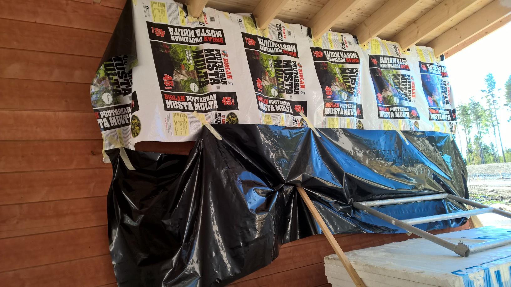 Kuultokäsitelty varaston seinä on varmuuden vuoksi suojattu muovilla, kun maalataan autokatoksen kattoa.