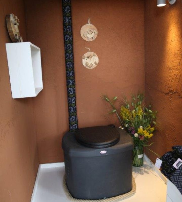Ulkohuussissa on punasaviset seinät. Kompostikäymälän ilmaputkessa on neulepaja Kainon Kielo-kuosinen suojus.
